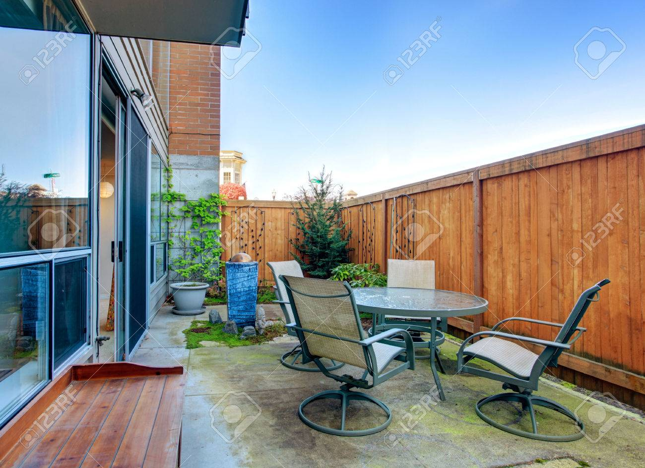 small fenced backyard with patio table set stock photo picture