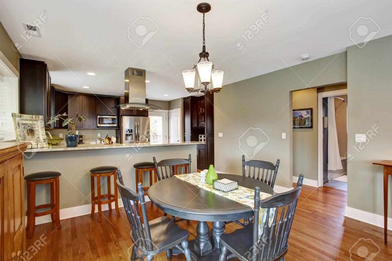archivio fotografico scuro marrone sala cucina con tavolo rotondo rustico da pranzo con sedie
