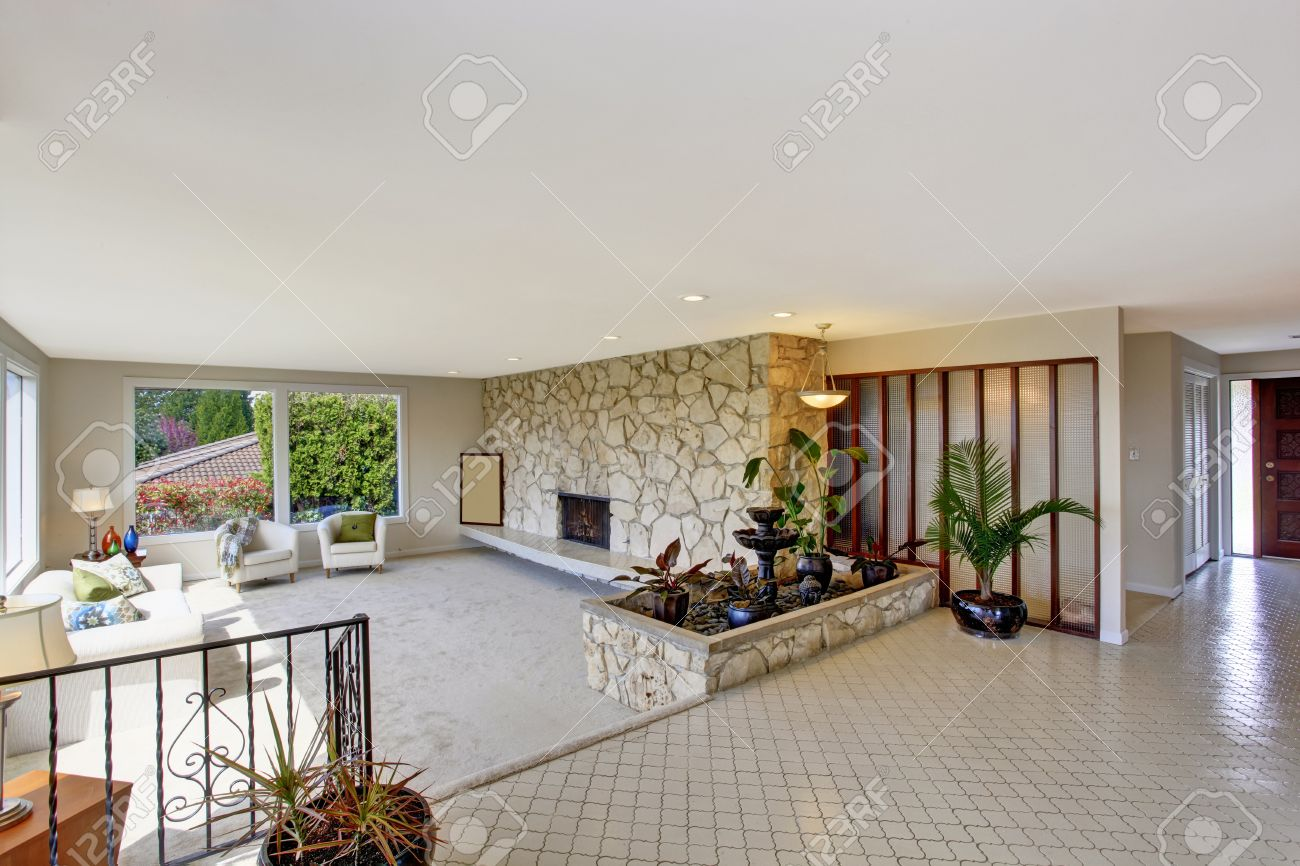 Bright living room with fountain in luxury house view of entrance bright living room with fountain in luxury house view of entrance hall with tile floor dailygadgetfo Choice Image