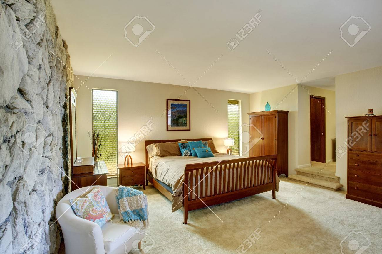Exceptional Soft Ivory Bedroom Interior With Rock Wall Furnished With Brown Wooden  Furniture Set Stock Photo