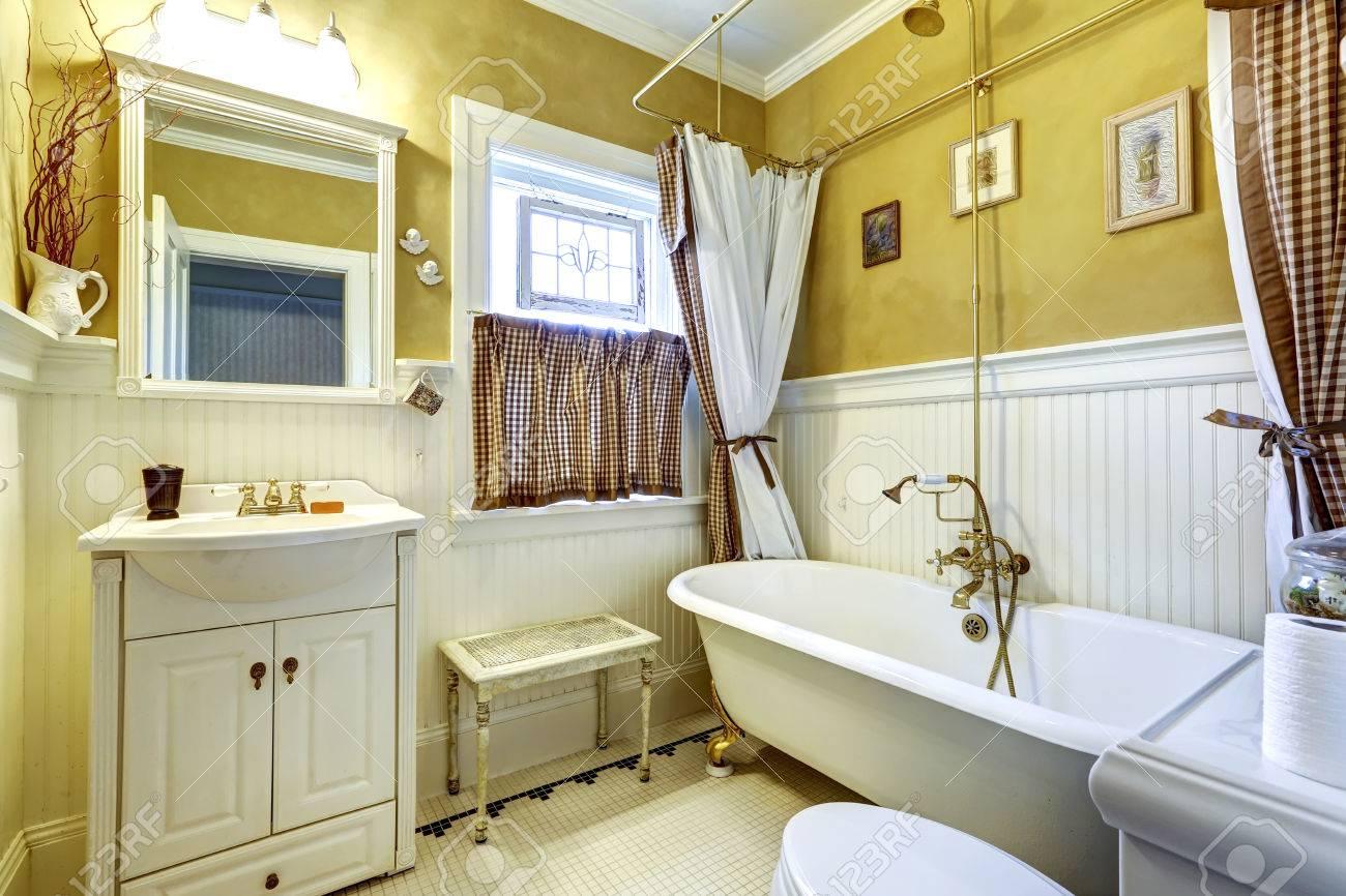 Intérieur de salle de bains ancienne jaune avec planche blanc lambrissée  assiette murale et antique vanité et baignoire