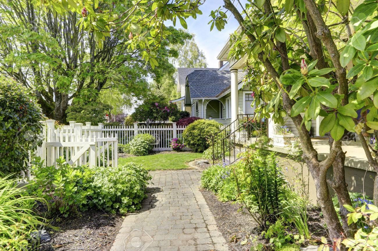 haus außen. blick auf vorgarten mit zaun und whiite offene tor