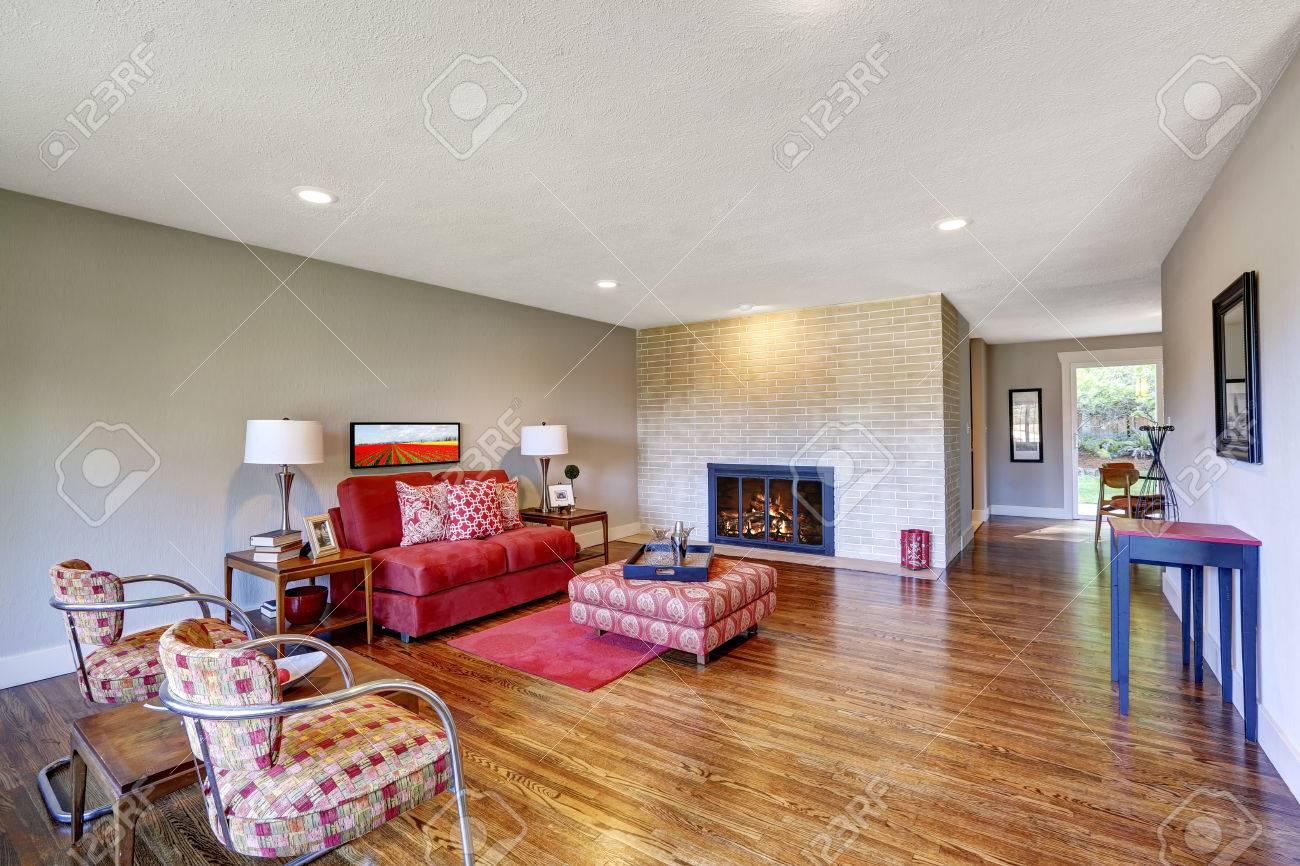 Ruime moderne woonkamer met heldere rode meubels en rood tapijt op ...