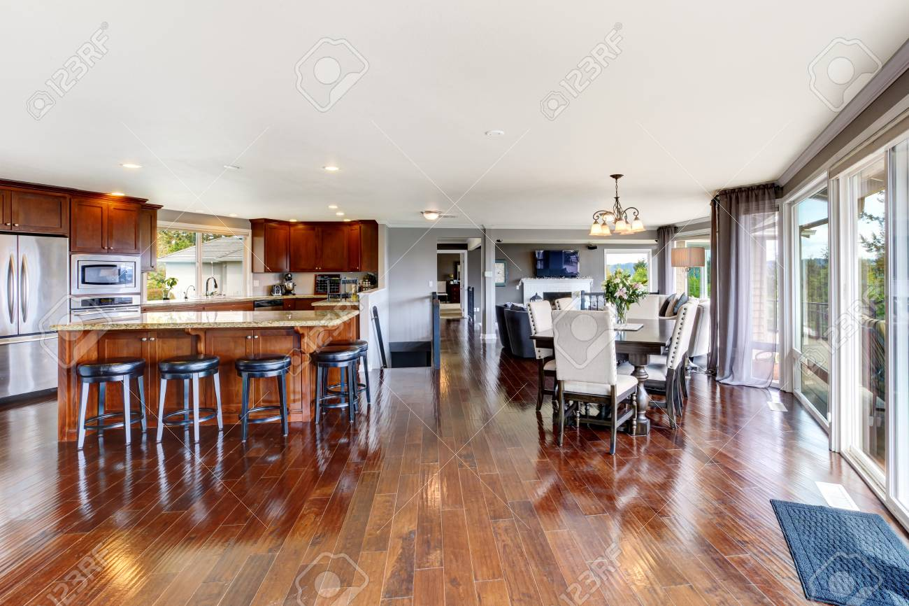 Spacious luxury kitchen room interior with kitchen island and black stools view of dining table set