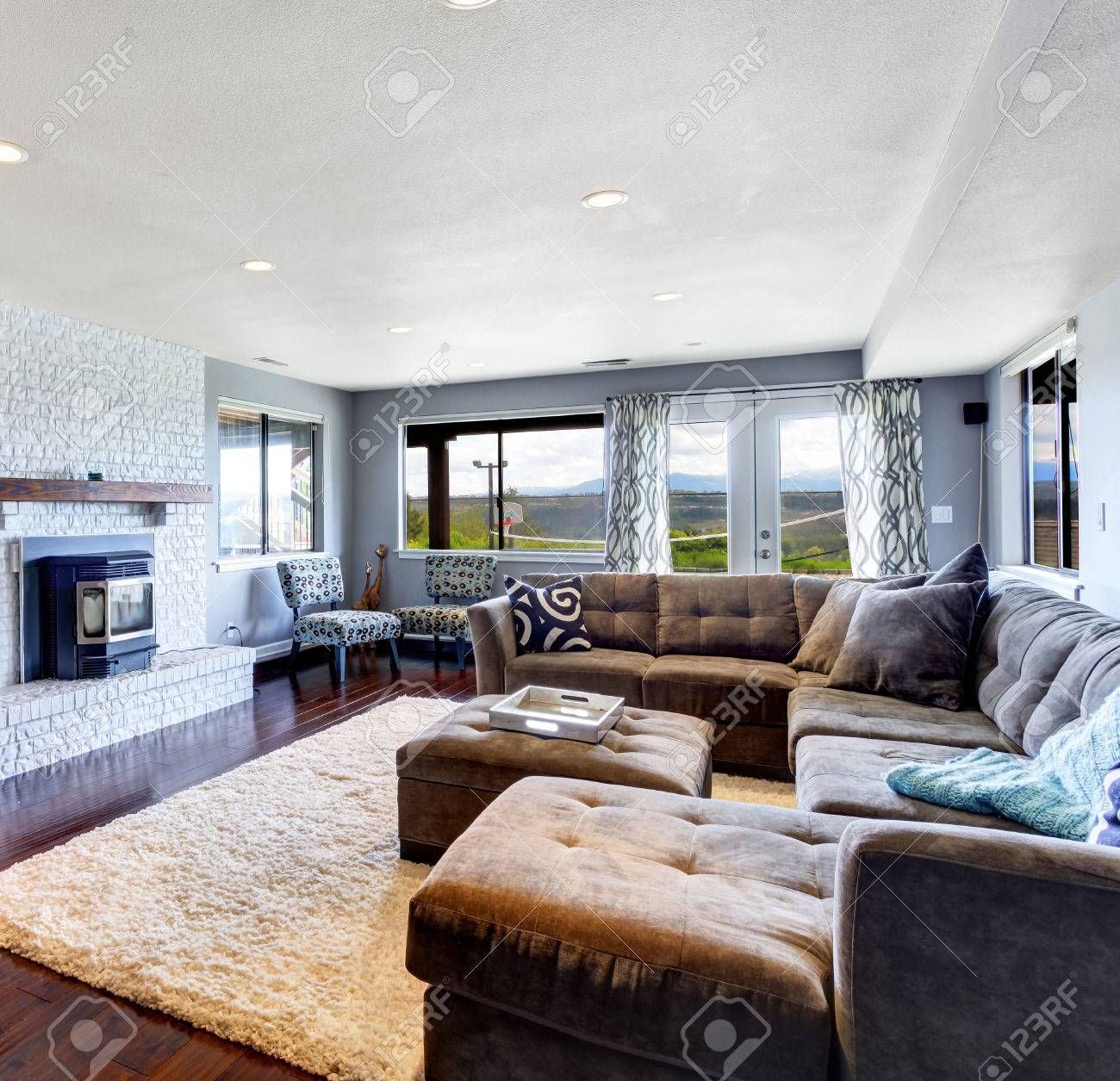 Living room with large comfortable sofa  soft ivory rug  cozy fireplace and  tv Stock. Living Room With Large Comfortable Sofa  Soft Ivory Rug  Cozy