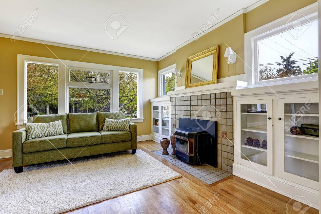 Vie lumière chambre jaune avec cheminée, un canapé vert et armoires blanches