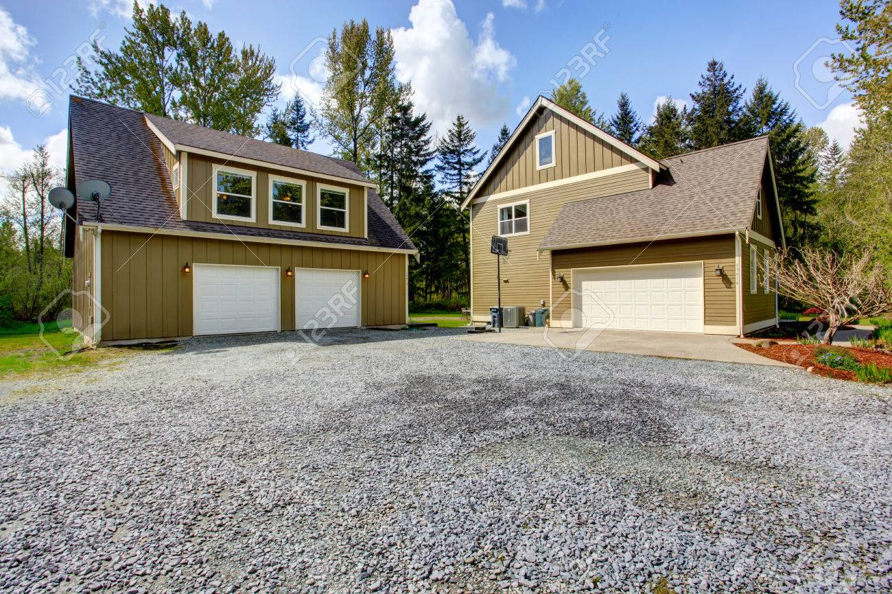 Countryside House Exterior With Garage. View Of Entrance And Gravel  Driveway Stock Photo