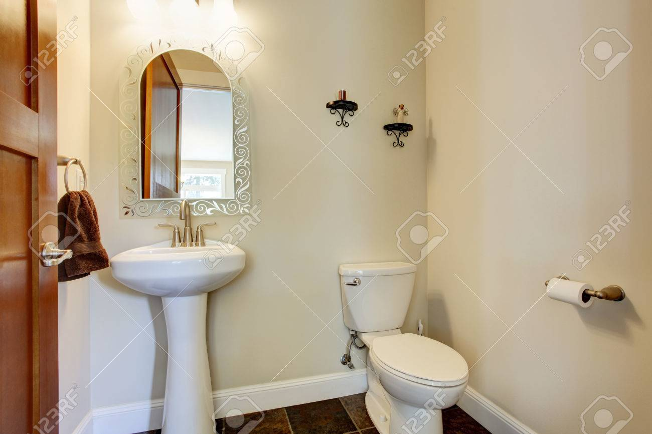 Small bathroom interior with dark brown tile floor white toilet small bathroom interior with dark brown tile floor white toilet and washbasin stand stock photo dailygadgetfo Image collections