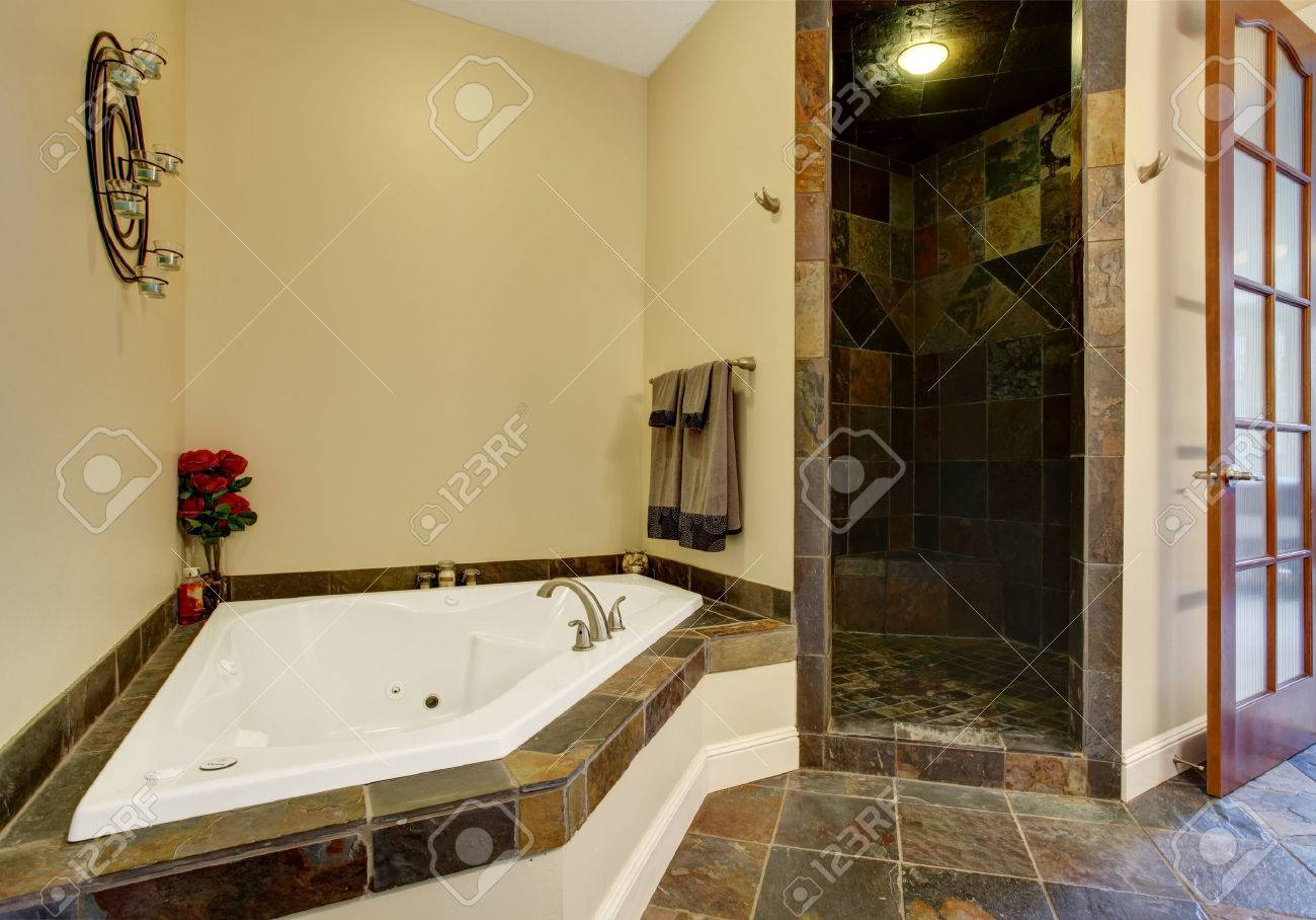 Interno bagno con pavimento di piastrelle scuro e doccia ...