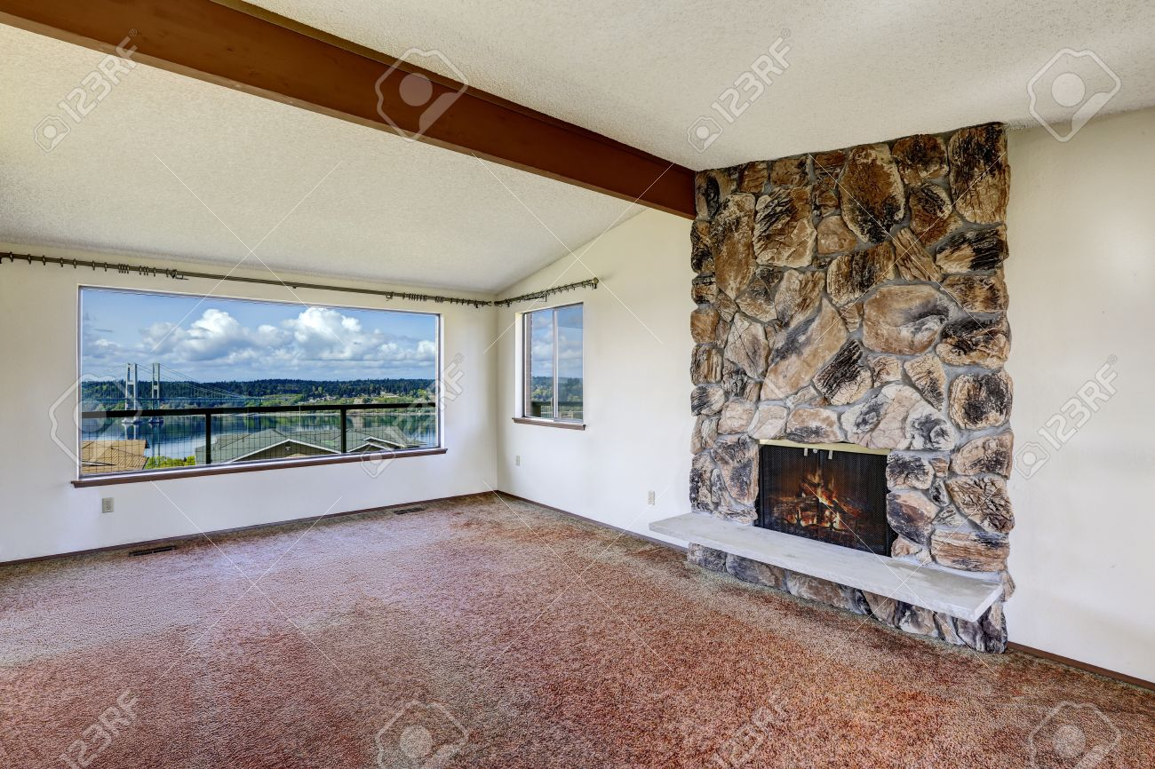 Empty living room with carpet - Bright Empty Living Room With Rocky Fireplace Vaulted Ceiling With Beam Brown Carpet Floor