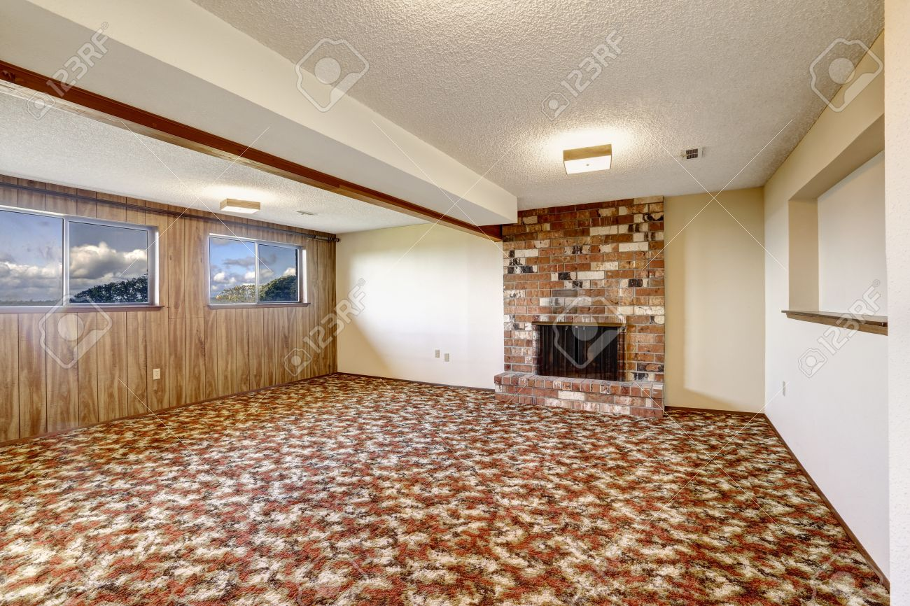 Empty living room with carpet - Empty Living Room With Brick Fireplace Wooden Plank Paneled Wall And Colorful Carpet Floor Stock