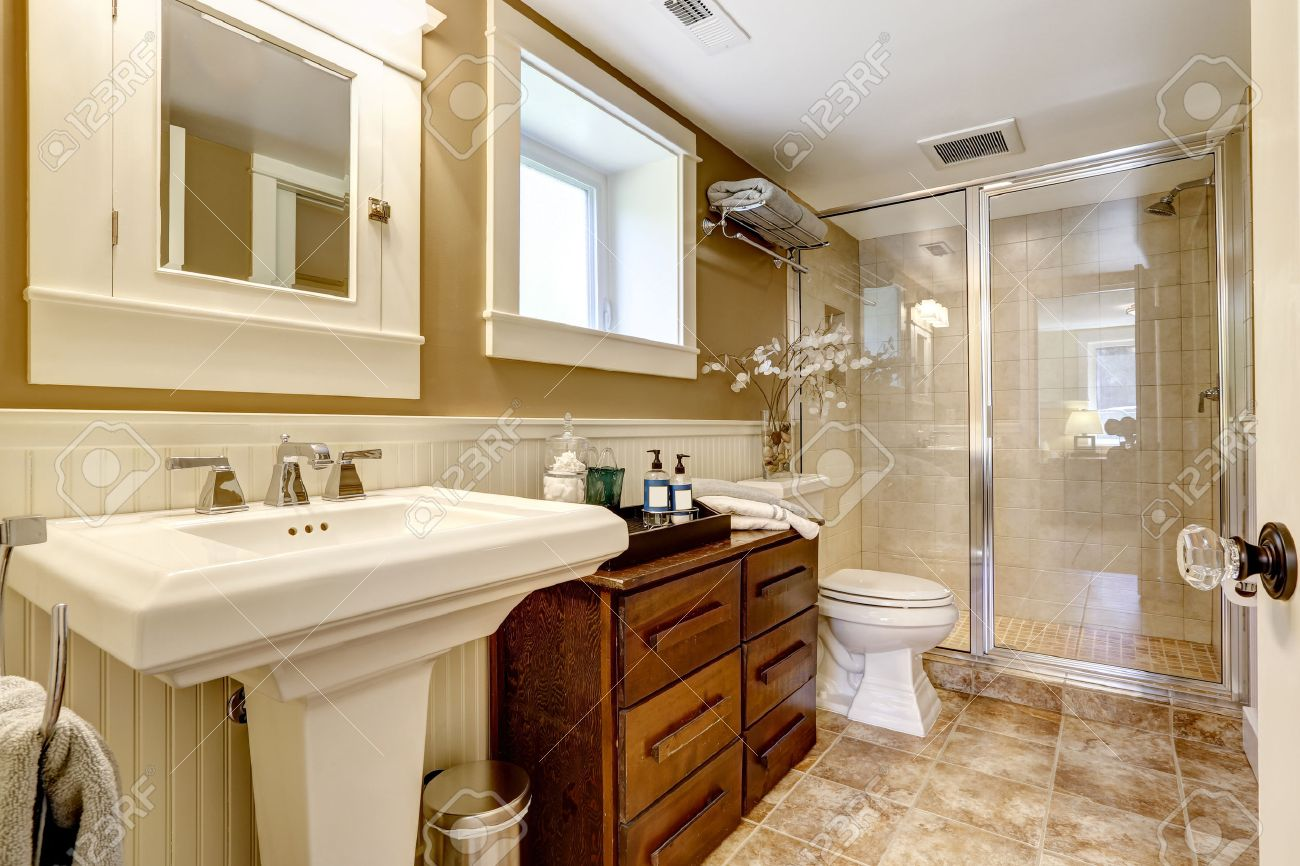Intérieur de salle de bains moderne avec armoire en bois, porte de douche  en verre et un support de lavabo