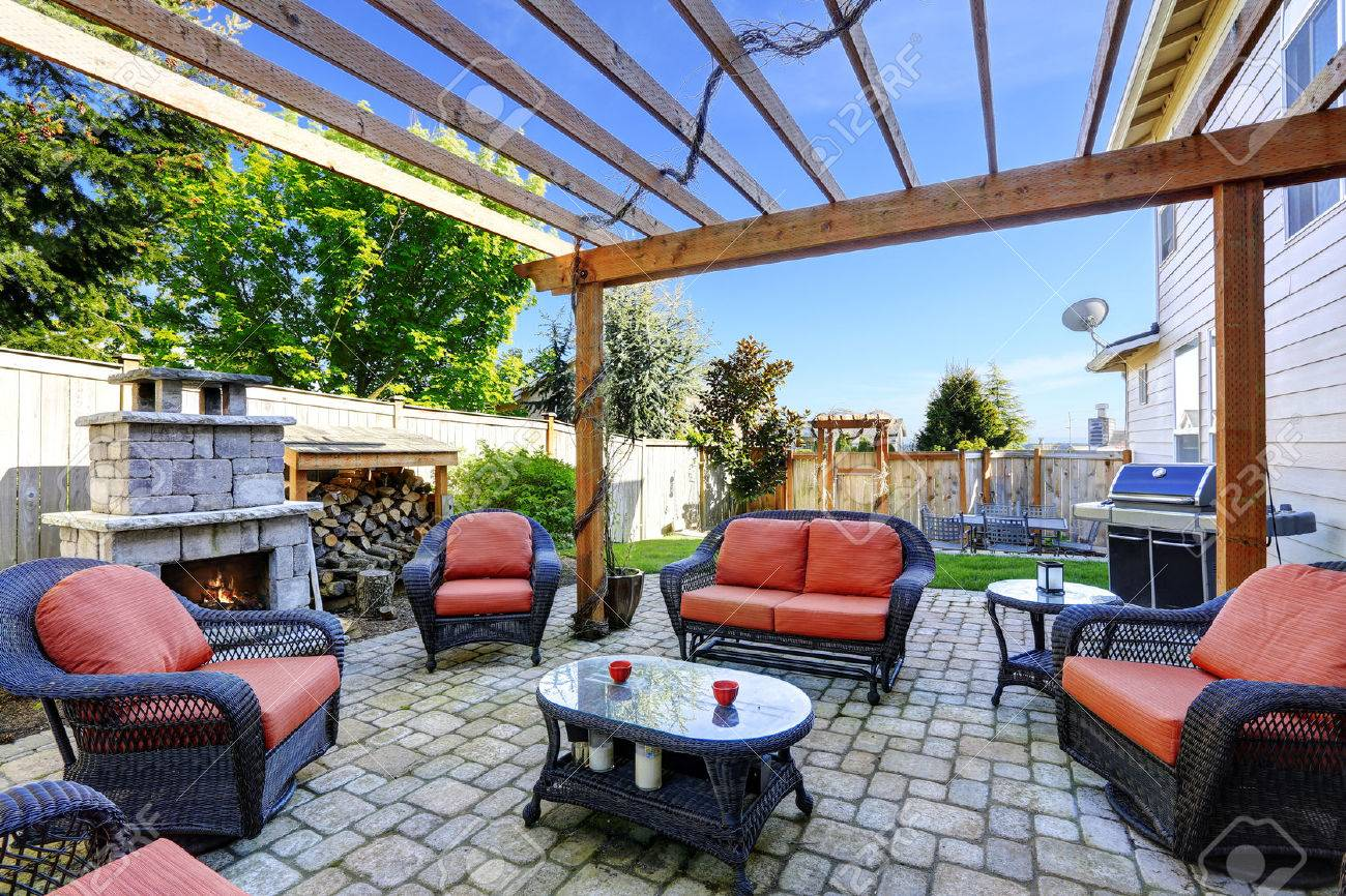 backyard cozy patio area with wicker furniture set and brick