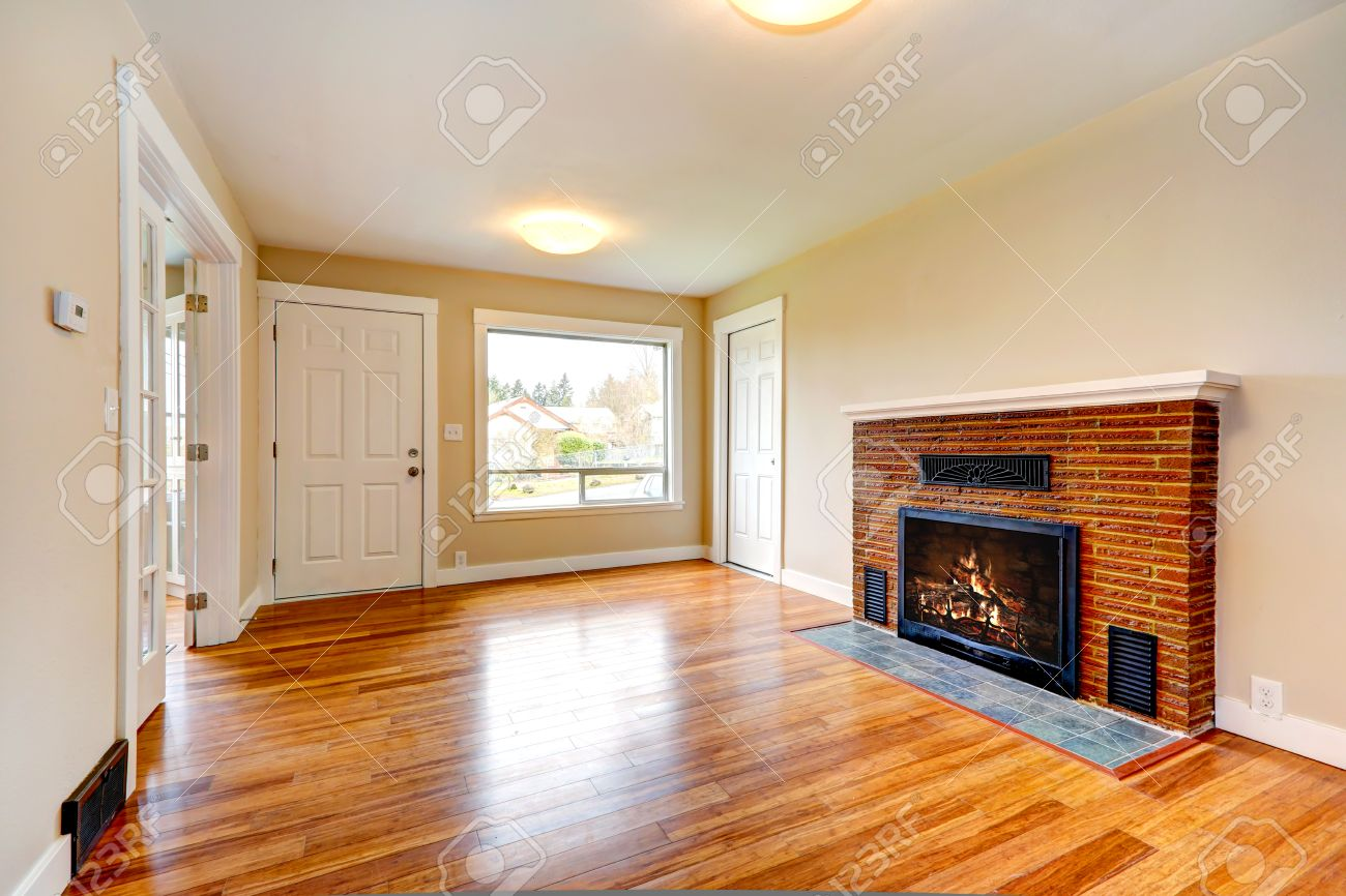 Bright Empty Living Room In Soft Ivory Color With New Hardwood Floor And Brick Background Fireplace