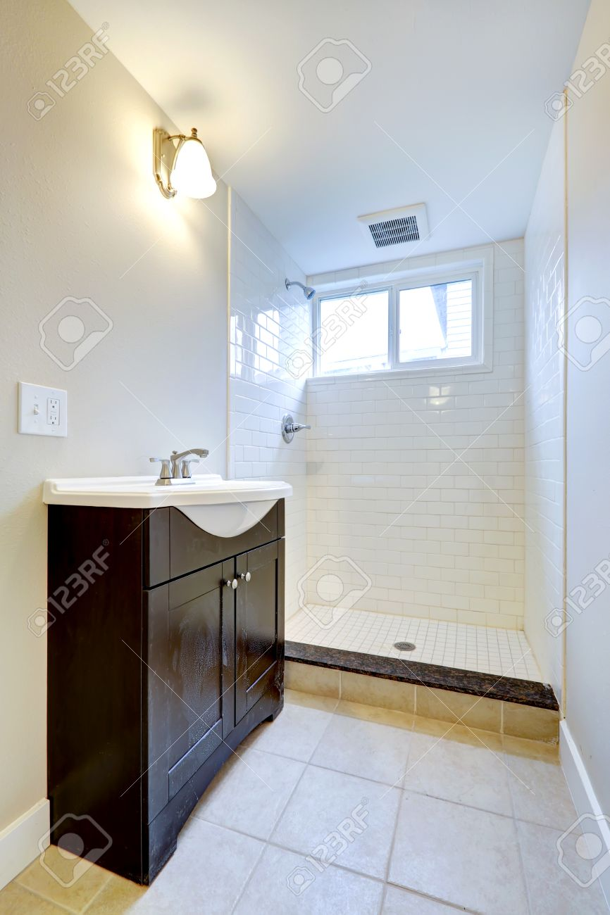 Bright Empty Bathroom Interior With Small Window One Vanity Cabinet And Open Shower Stock Photo