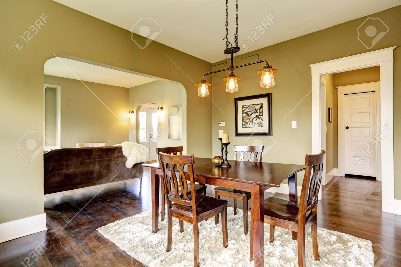 Open Floor Plan Dining Area With Dark Brown Table Set And Soft Rug On