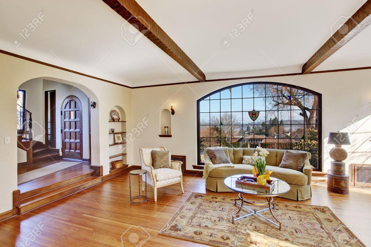 Doux ivoire salon lumineux avec fenêtre de voûte, plancher de bois franc et  de poutres apparentes