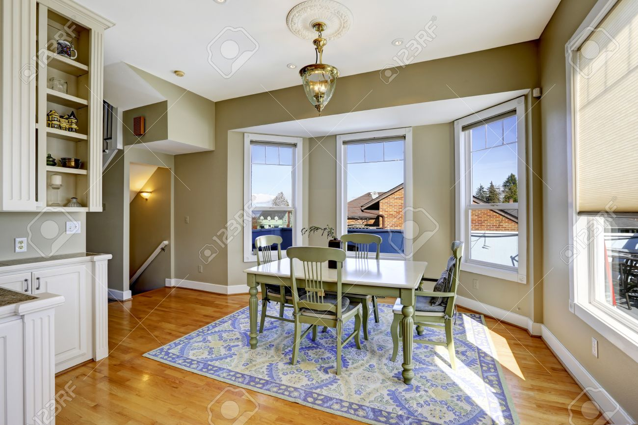 Dining Room In Light Olive Color With Hardwood Floor Blue Rug And Green Table
