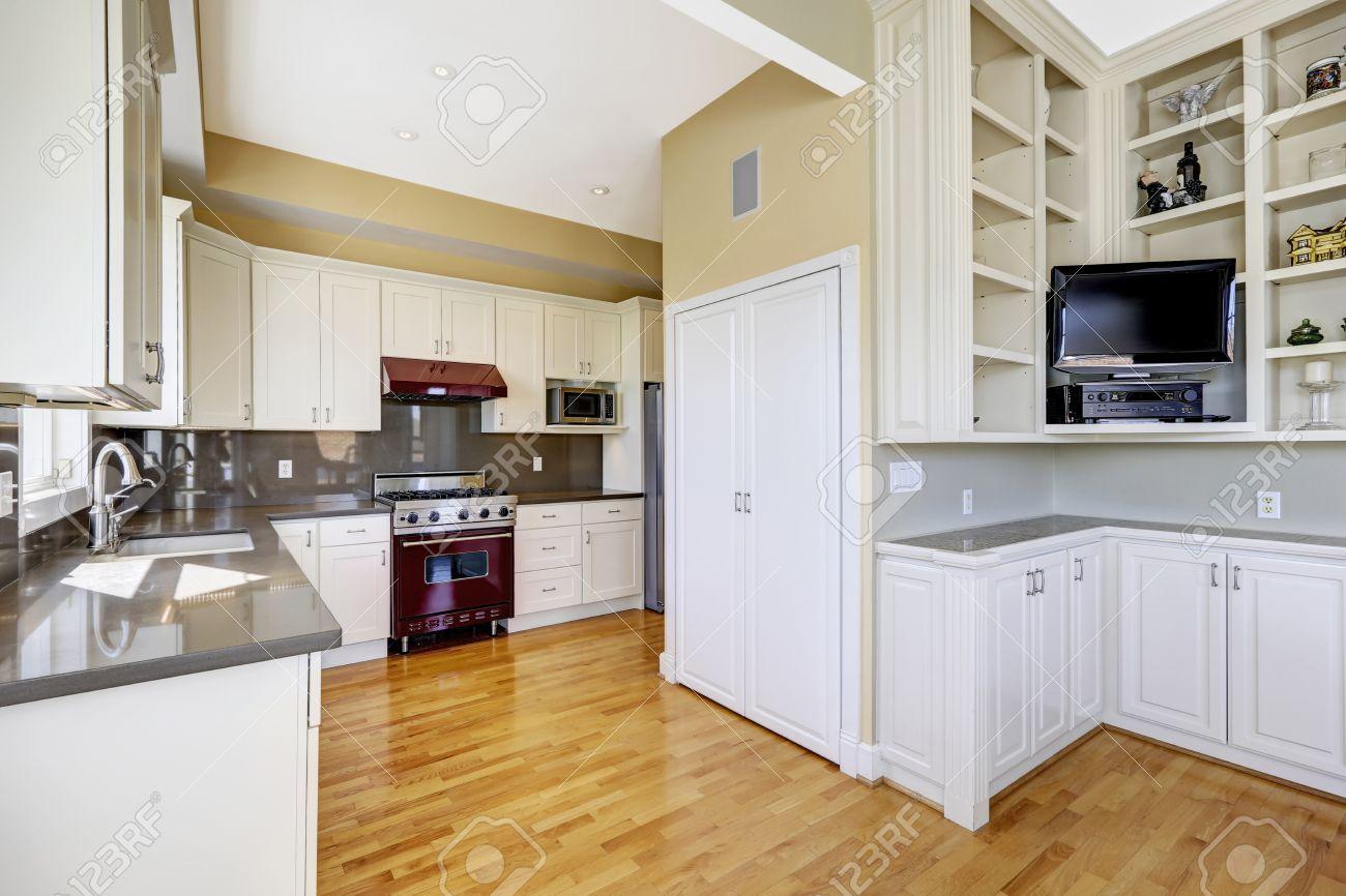 Lichte keuken kamer met hardhouten vloer, witte kasten en glanzend ...