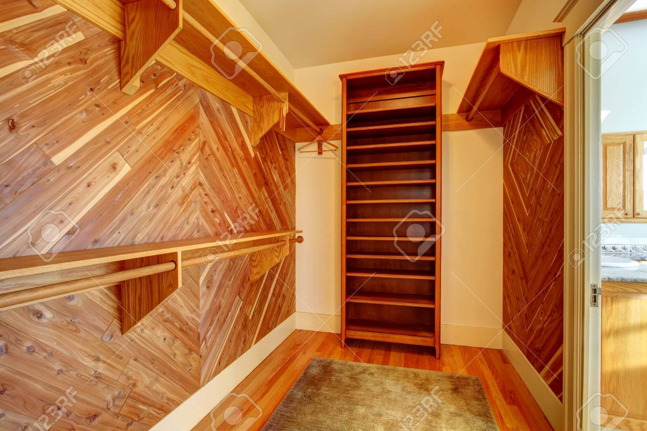 Emtpy Closet With Hardwood Floor And Wood Paneled Walls. View Of Shelves  And Hangers Stock