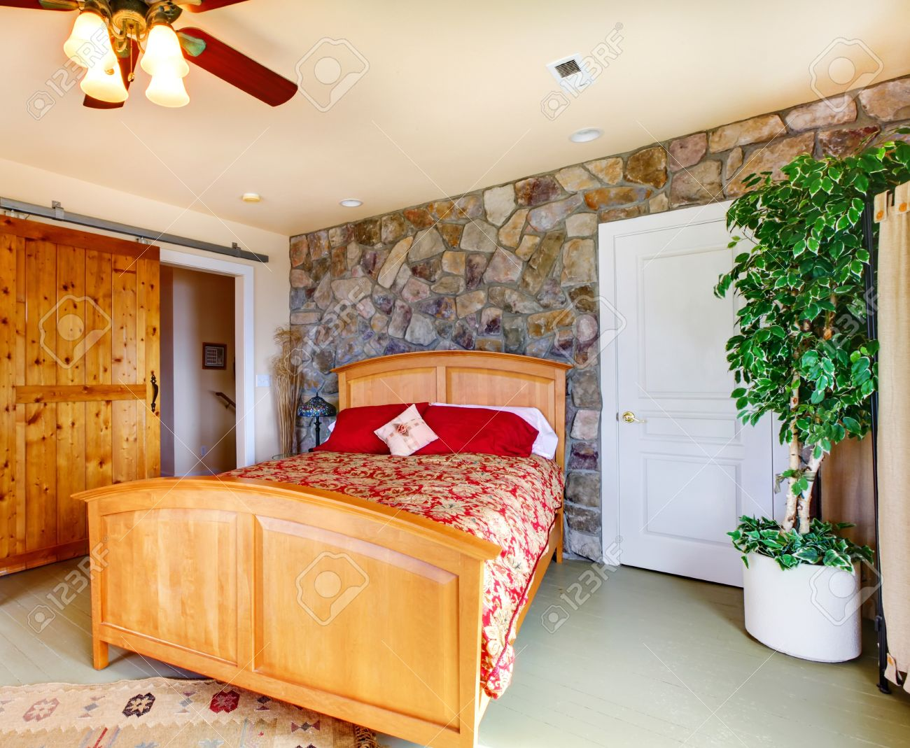 Exotic bedroom interior with stone wall trim wooden bed and exotic bedroom interior with stone wall trim wooden bed and decorative tree in corner stock amipublicfo Image collections