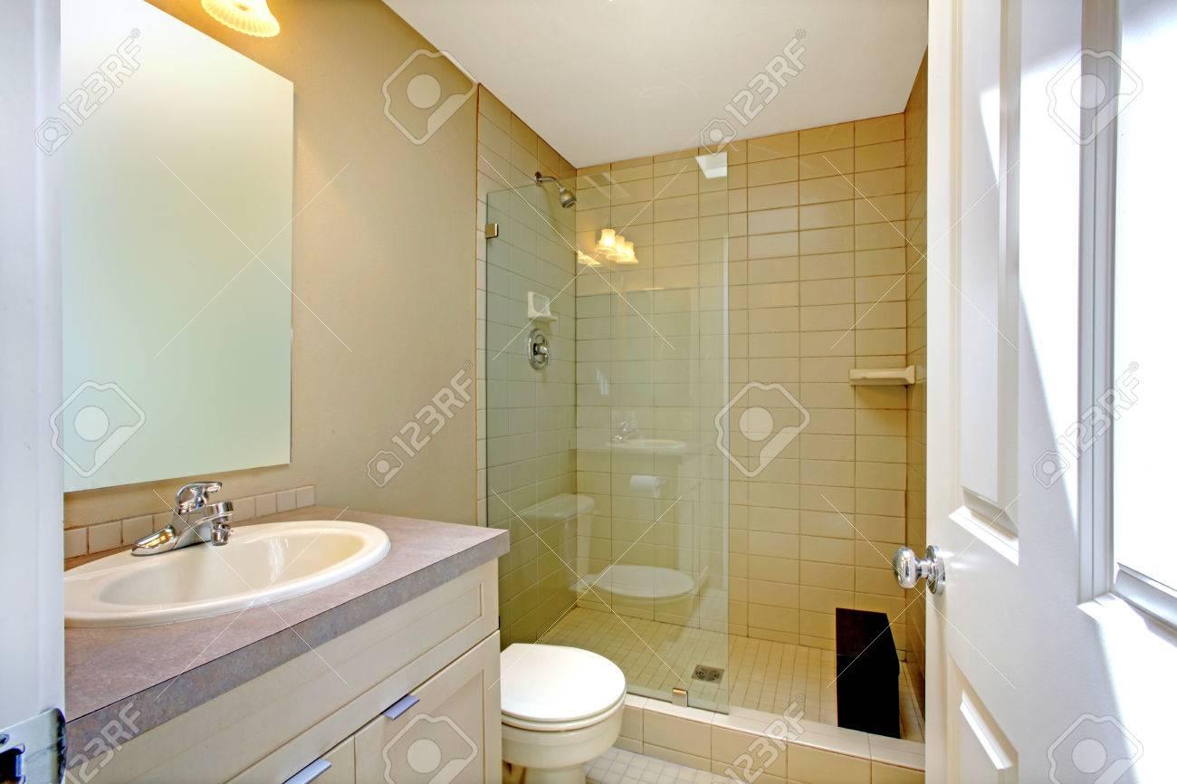 Pequeño cuarto de baño interior con gabinete de la vanidad mocha y ducha  con puerta de vidrio