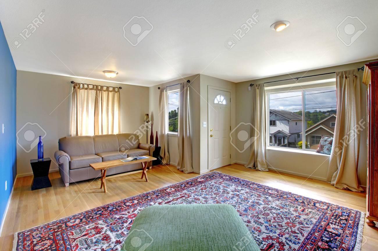 Salon avec mur bleu lumineux. Meublé avec chaise verte, canapé beige et  rustique table basse