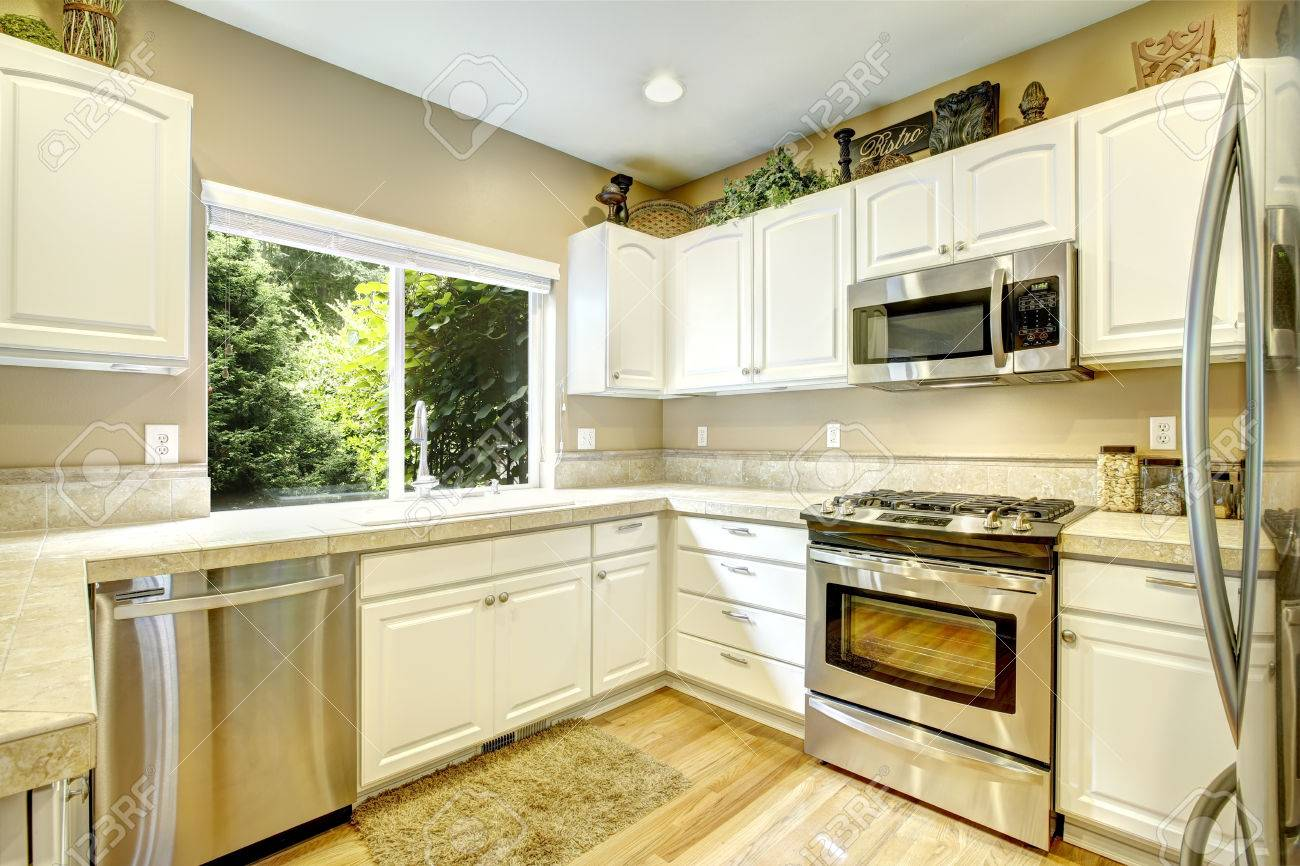 White Kitchen Cabinets With Steel Appliances And Light Tone Hardwood ...