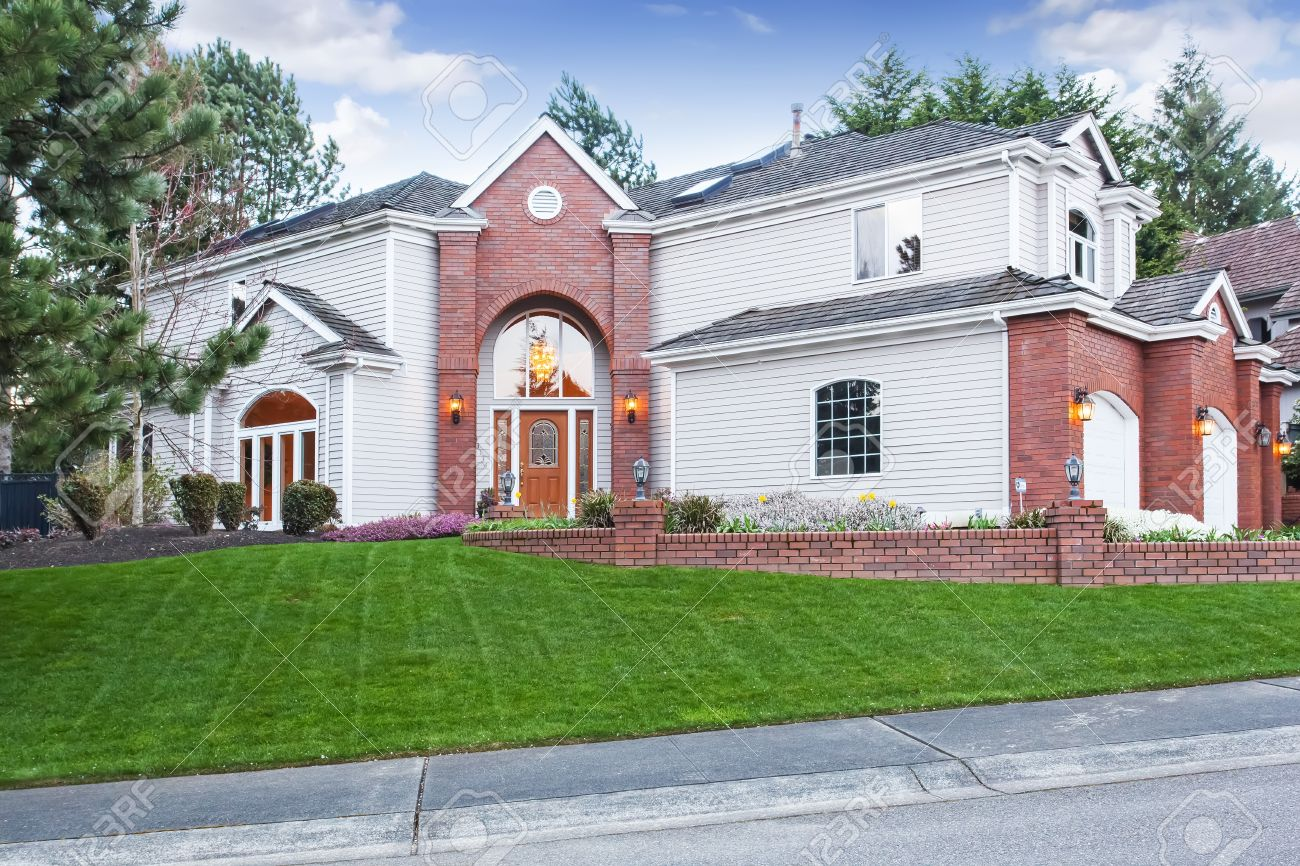luxury house exterior with red brick wall trim with three car garage and driveway stock