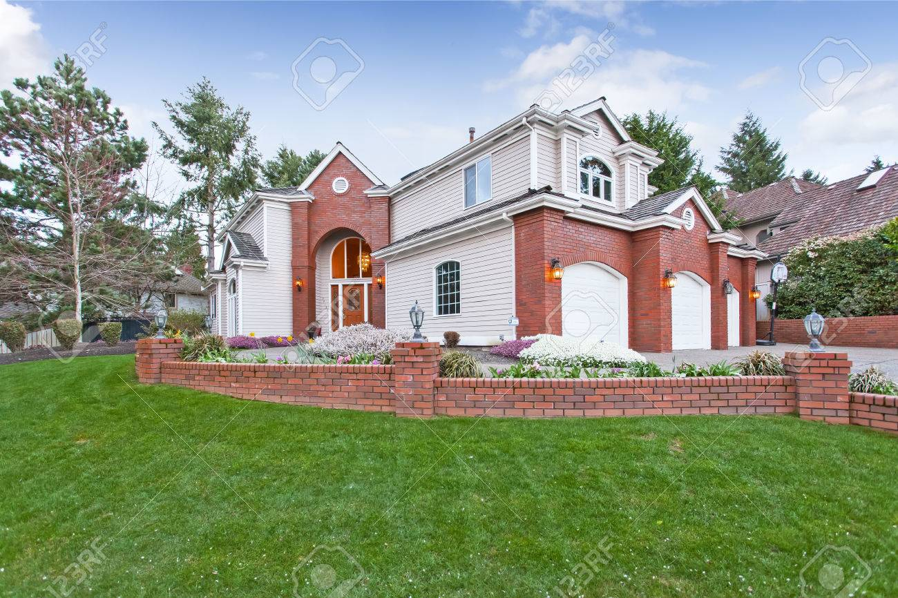 luxury house exterior with red brick wall trim with three car garage and driveway