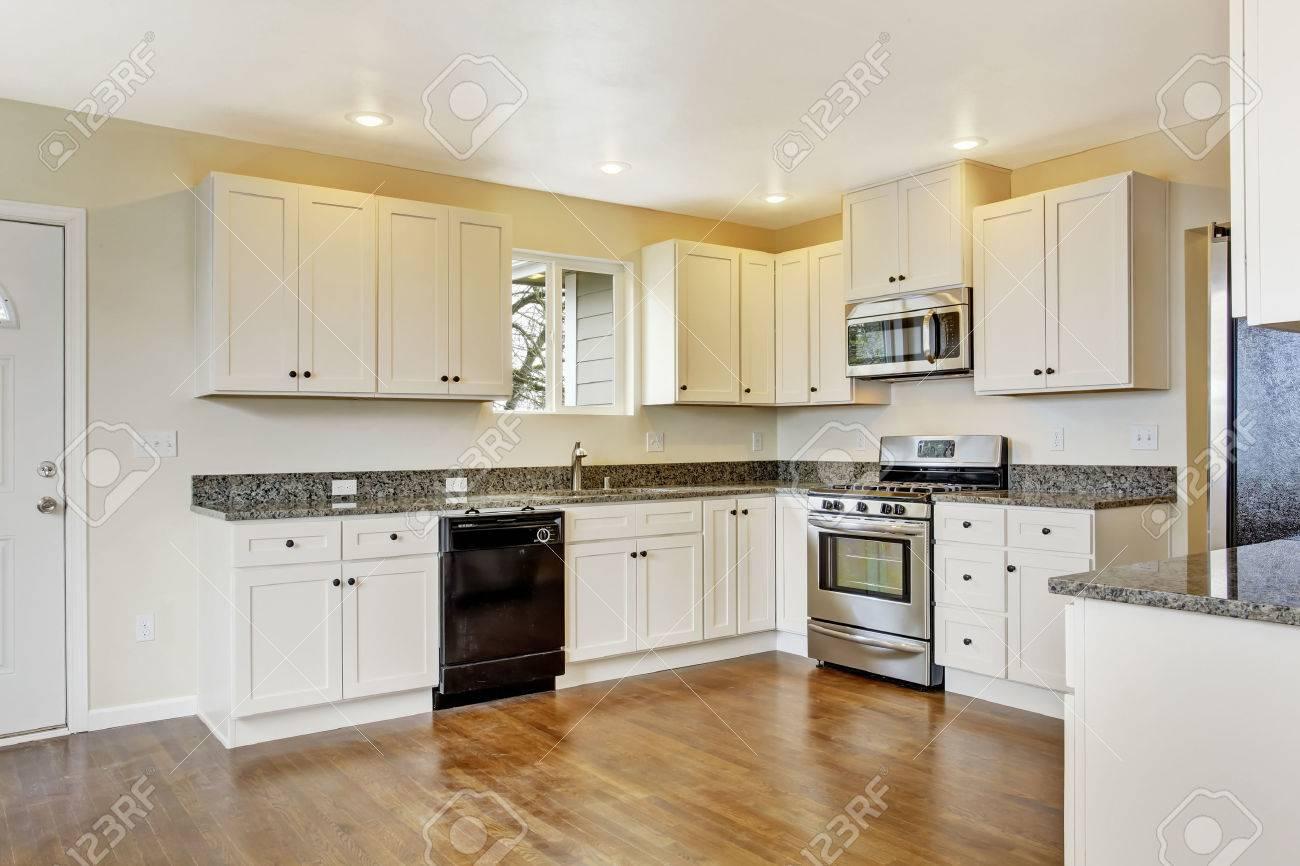 Interior de la casa vacía. Amplia cocina con muebles blancos, encimera de  granito y electrodomésticos de acero