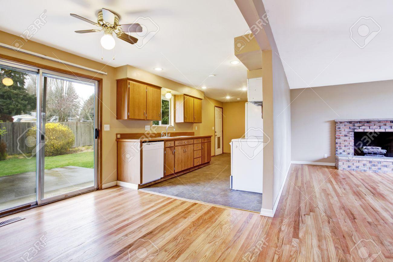 Interior de la casa vacía. Cocina con comedor vacío y la puerta deslizante  para patio trasero. Vista de la sala de estar con chimenea