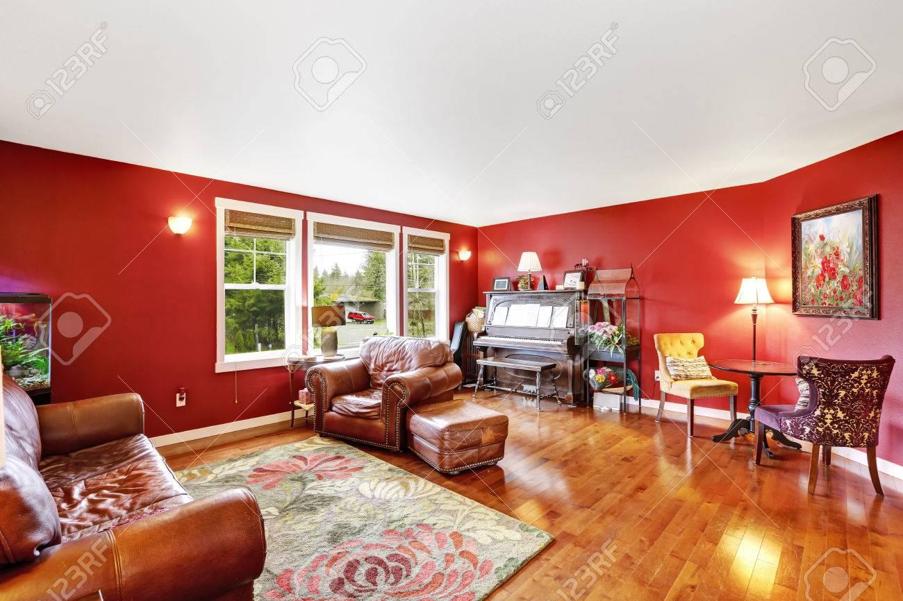 Heldere rode woonkamer interieur met bruine lederen counch ...