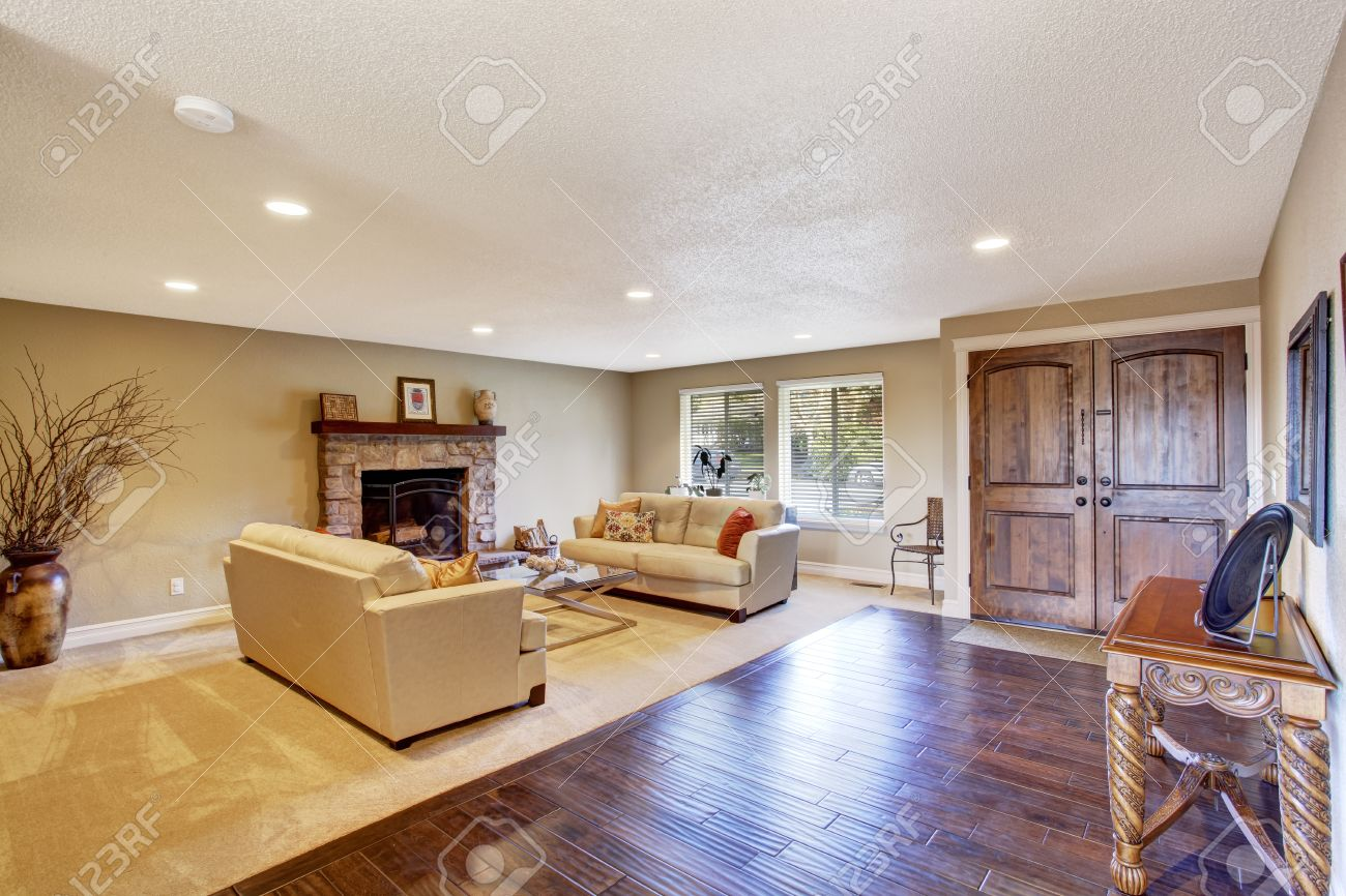 Light Tones Living Room With Fireplace And Two Couches View Of Entrance Hall Carved Wood