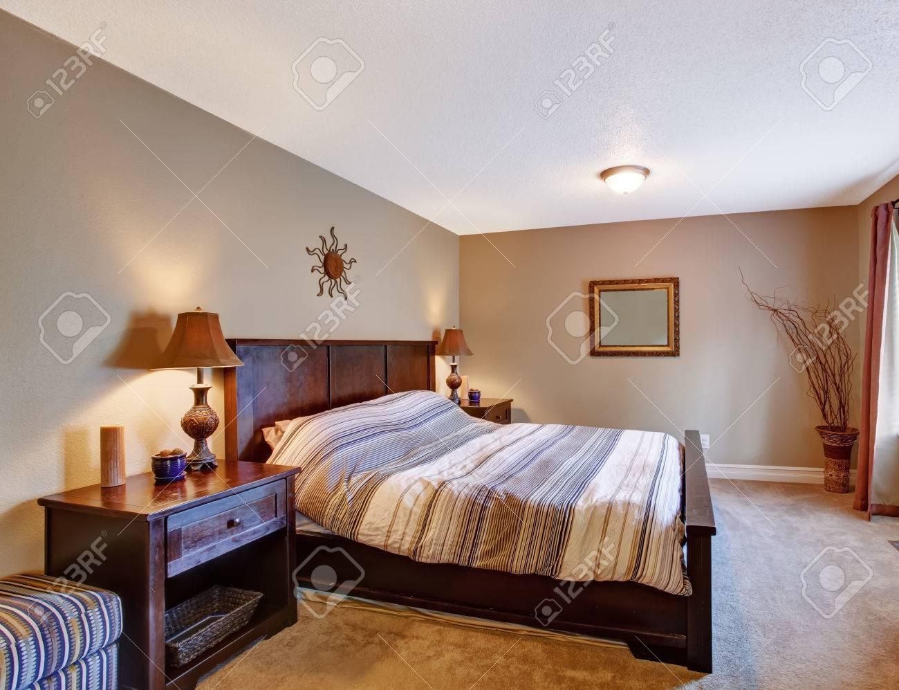 Camera da letto con letto a strisce, comò, spogliato pouf e comodino