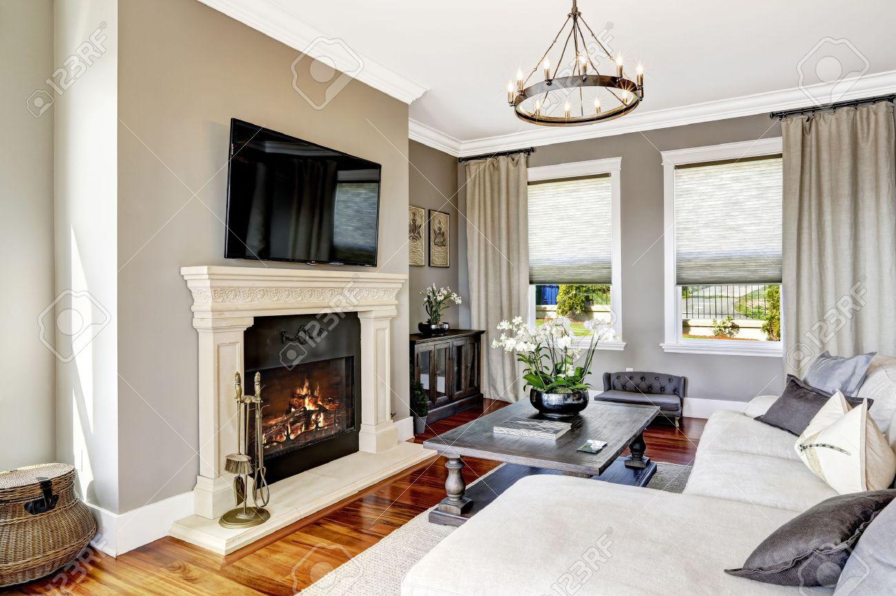 Helle Luxus Wohnzimmer Mit Kamin Und TV, Weiß Gemütliche Couch Und  Geschnitzten Holztisch Mit