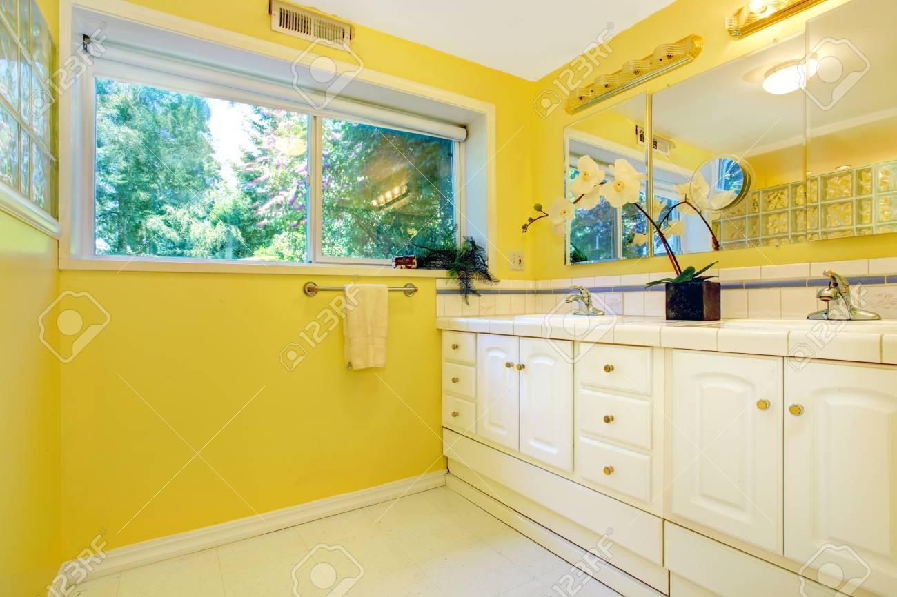 Intérieur de salle de bain jaune vif avec des armoires blanches
