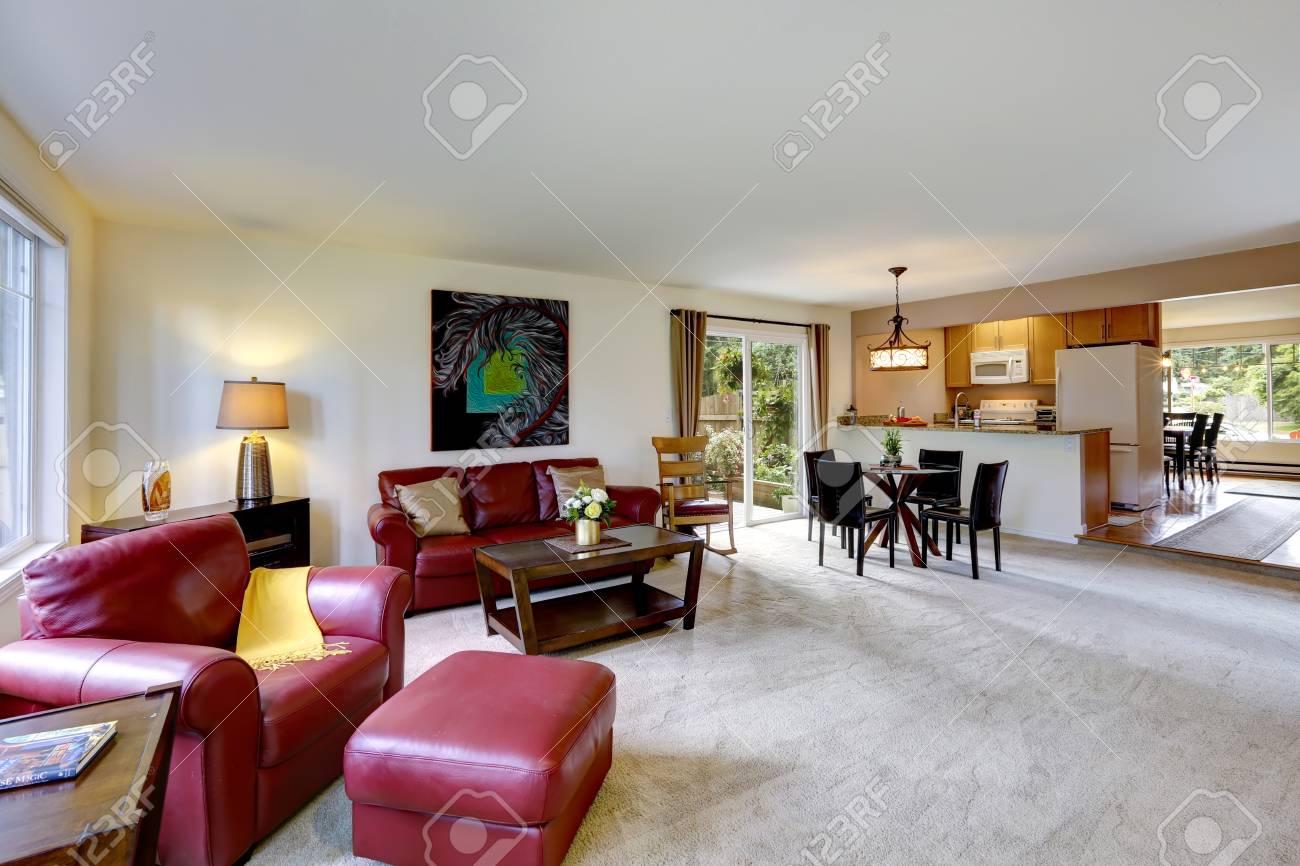 Luminoso soggiorno con divani in pelle rossa Vista della sala da pranzo e  sala cucina