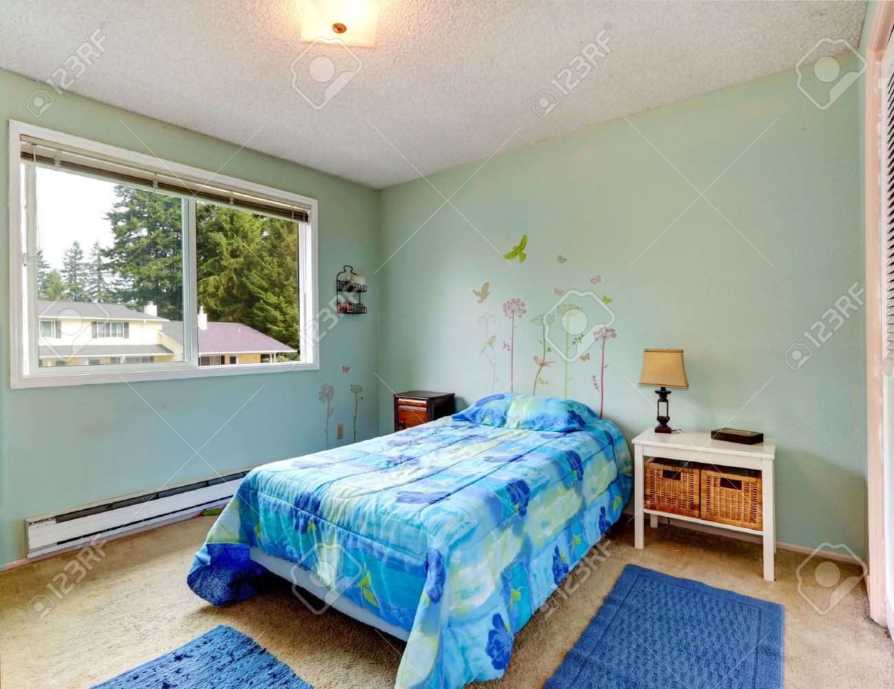 Aqua tones small bedroom interior with blue bed and rugs