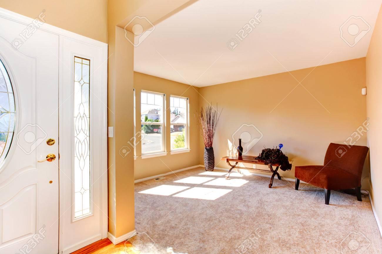 Maison vide. Vue de l\'entrée couloir avec porte blanche et une salle  décorée avec chaise et table en bois