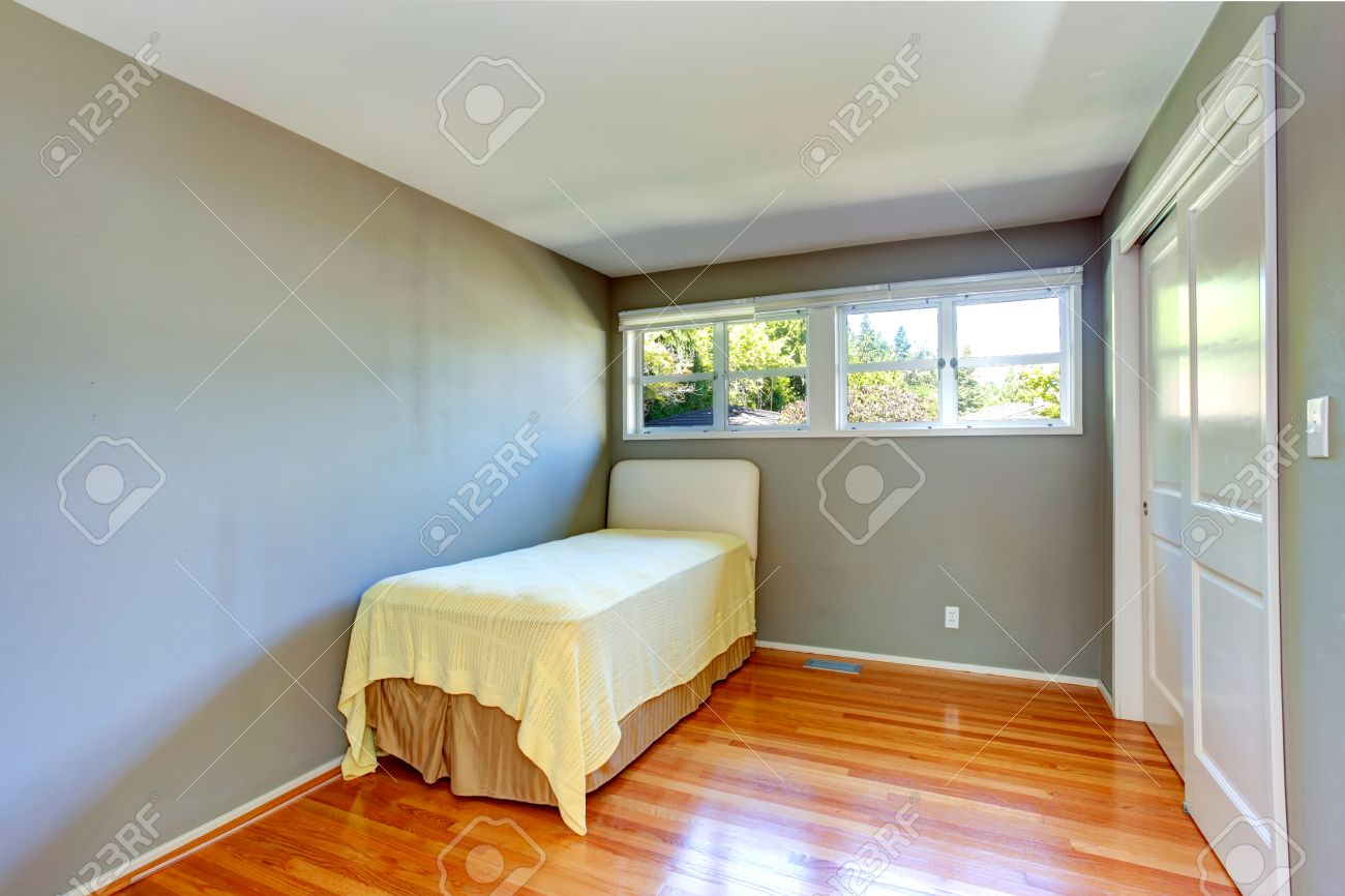 Empty Small Bedroom With Hardwood Floor And Grey Walls View Stock