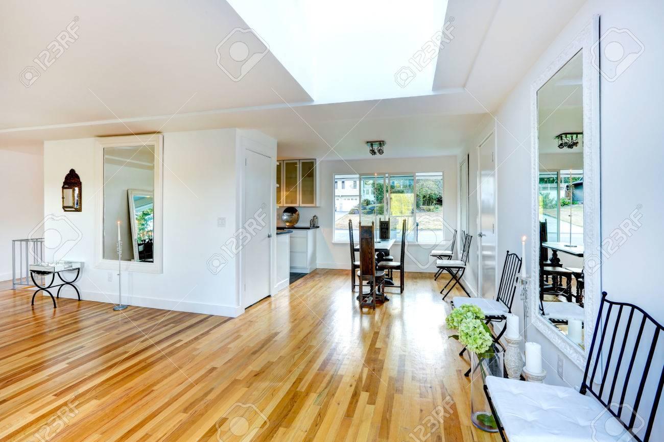 Helder wit woonkamer met hardhouten vloer. kleine dinig gebied ...