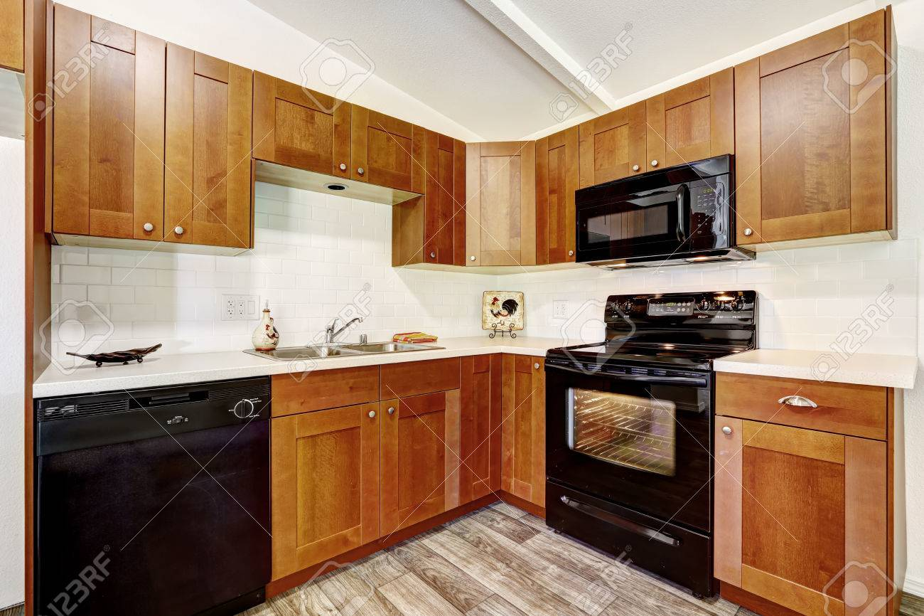 Kitchen Cabinets With Black Appliances And White Tile Wall Trim Stock Photo Picture And Royalty Free Image Image 30963378