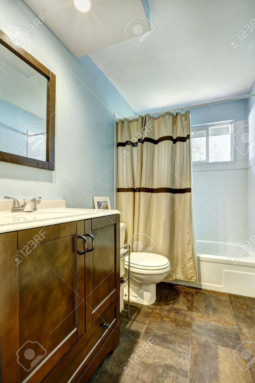 Bathroom With Brown Tile Floor And Light Blue Walls Wooden Brown Vanity Cabinet And Beige
