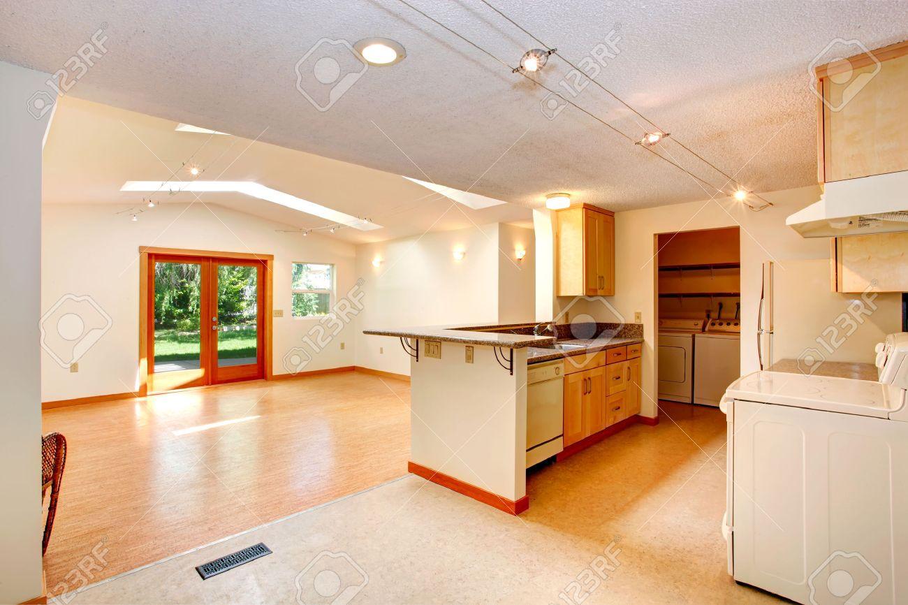 Banque dimages , Intérieur de la maison vide avec plan détage ouvert. Séjour avec plafond voûté et puits de lumière. Vue de coin cuisine