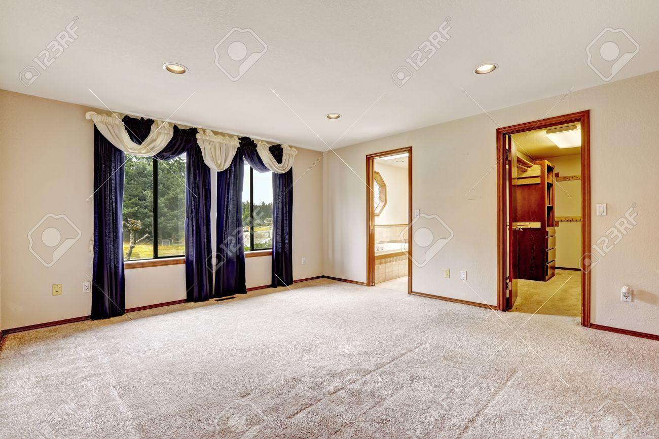 Intérieur de la chambre vide de maître avec placard et salle de bains de  plain-pied. Chambre décorée avec des rideaux pourpres