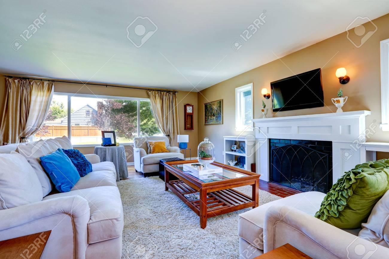 Wohnzimmer mit kamin und fernseher  Weicher Beige Wohnzimmer Mit Weißen Möbeln, Glasplatte Tisch ...