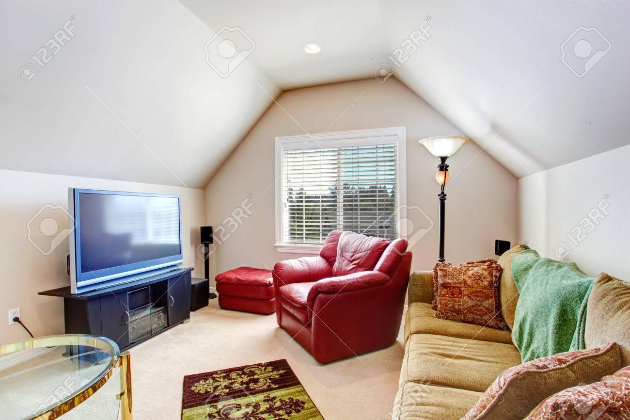 Salon avec plafond voûté. Meublé avec un fauteuil rouge vif, canapé marron  et tv