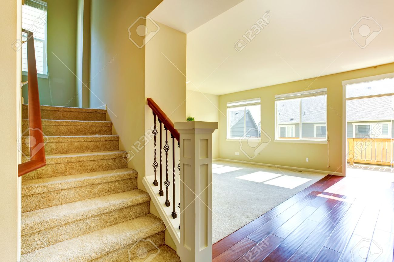 Empty living room with carpet - Ivory Living Room With Carpet Floor And Hallway With Hardwood Floor And Staircase In Empty House