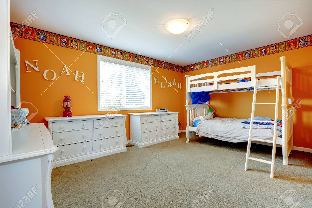 Bright Orange Kids Room With White Dressers And Bulk Bed Stock Photo